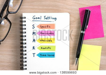 Hand writing definition for smart goal setting on notebook with pen eye glasses and colorful sticky note on desk