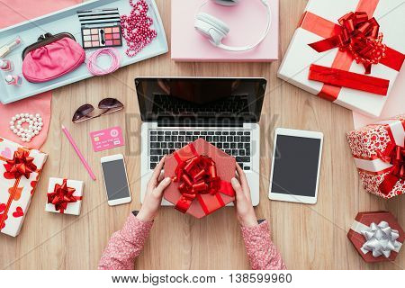 Female customer receiving a beautiful gift she is shopping online using a laptop and a credit card e-commerce and technology concept