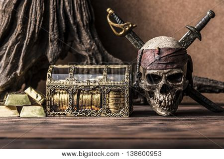 still life photography with pirate skull holding two swords and treasure coffer gold bar bullion. Halloween concept