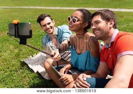 Cheese. Happy and merry youth making selfie photo using mobile phone and selfie stick while sitting on the grass in the park and communicating