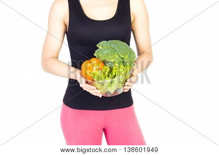 Woman holding bowl with fresh vegetables near the waist. Diet and nutrition.