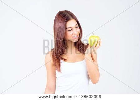 Beautiful young woman looking at apple. Healthy lifestyle.