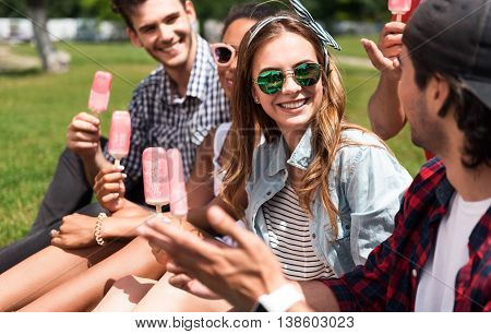 Cool summertime. Positive and delighted group of young people holding ice cream while sitting in the park together and communicating