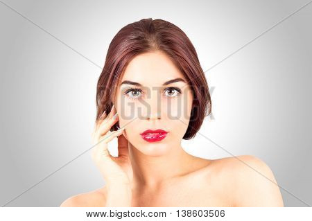 Sexy young woman with beautiful red lips looking at camera on gray background. Beauty woman with red lips touching cheek.