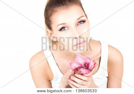 Portrait with permanent make up holding pink flower.