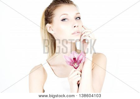 Beautiful woman with a proud look. Woman with clean and smooth skin. Woman with pink flower. Moisturize.