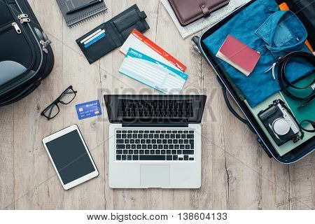 Traveler packing and getting ready for a trip desktop with baggage tickets credit card laptop and digital tablet flat lay