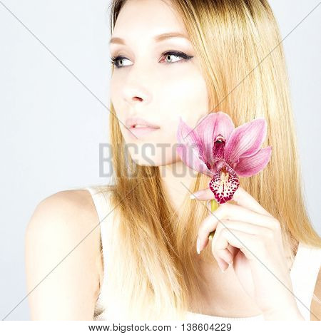 Attractive beautiful blonde with a pink flower. Woman with permanent makeup. Close up portrait of blonde.