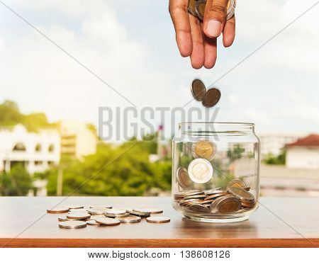 Close up of glass bottle stacking silver coins falling on wooden table, Save money for prepare in the future Vintage style