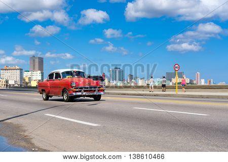 HAVANA,CUBA - JULY 14,2016 :  Classic car on the Havana malecon avenue with a view of the city skyline