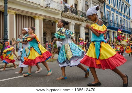 HAVANA - CUBA JUNE 9, 2016: Dancers in colorful costumes celebrate Havana Day with a parade along Paseo de Marti in the historic La Habana Vieja neighborhood.