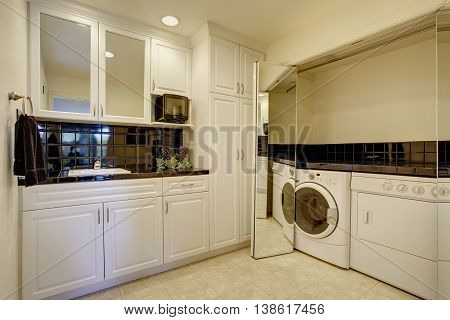 Small kitchen room with white cabinets and black back splash trim. Room has a built-in laundry area with washer and dryer