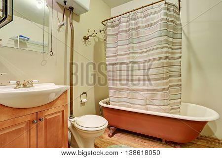 Antique Bathroom Interior With Brown Bath Tub And Hardwood Floor