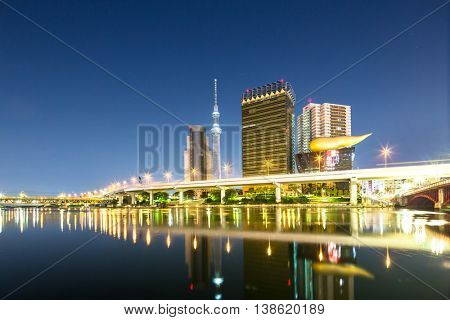 modern office buildings and elevated bridge near tokyo tower in downtown of tokyo in blue sky at night