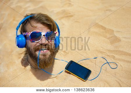 Guy with headphones buried in the sand on the head