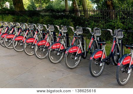 London, England - July 10, 2016: Row of red bicycles for rent in Hyde park docking station, offered for tourists and locals as an efficient transportation method.