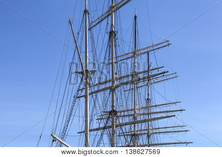 The masts and rigging on a full-rigged ship. Sky and some visible clouds.
