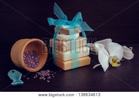 Spa setting in purple and blue colors with different kind of natural soaps, orchid and the wooden pounder on dark wooden background. Tower stack of different handmade soaps. Selective focus.