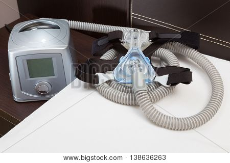 Sleep Apnea CPAP mask hose headgear and machine on bed selective focus on CPAP mask
