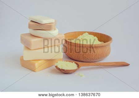 Spa setting with different kind of natural soaps and sea salt in wooden bowl on white background. Bar of natural handmade soap. Tower stack of different handmade soaps on white. Selective focus.