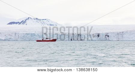 Expedition or tourist boat in front of the large and massive Borebreen glacier. Arctic environment in Oscar II Land at Spitsbergen, Svalbard.