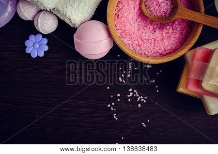 Composition of spa treatment on the dark wooden table. Spa and wellness setting with natural soap, sea salt and towels in purple, pink and violet colors. Top view. Copy space.