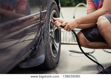 Man Driver Checking Air Pressure And Filling Air In The Tires Of Car