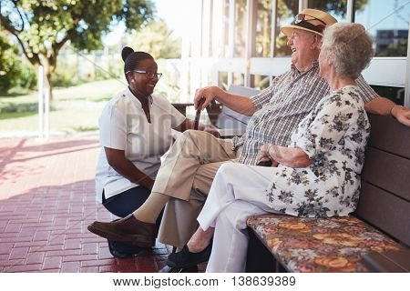 Portrait of loving retired couple relaxing on a bench outside their house with a female nurse sitting by. Caucasian elderly man and woman sitting relaxed on a bench with home caregiver at old age home.