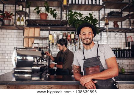 Male Coffee Shop Owner Standing At The Counter