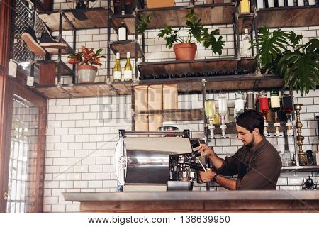 Side view shot of a male barista making a cup of coffee. Young man standing behind the cafe counter preparing coffee using coffee maker machine.