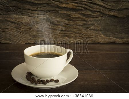 Warm cup coffee and saucer on a wooden table. Dark background. Space for your text.