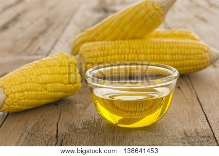 Closeup corn oil on a wooden table.