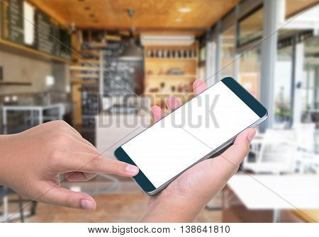 Human hand hold and touch screen smart phone tabletcellphone on blurred in cafe background; With clipping path on screen Smart Phone. blank screen for your advertising.