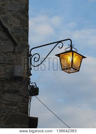 Vintage street lamp in medieval village at twilight. Tuscany Italy