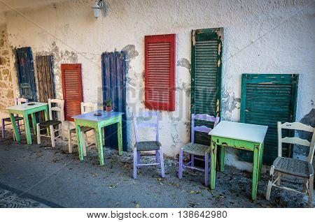 Old tables and seats on street. Green and white tables and white and purple seats near blue, green and red windows on a street in Crete island, Greece.