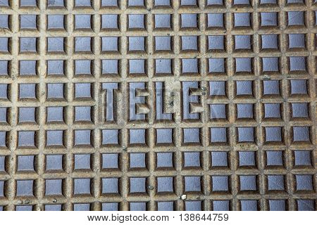 steel gray manhole cover and the word TELE