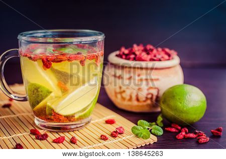Fresh antioxidant herbal tea from goji berries and lime in glass cup. Wolfberry for a healthy diet. Healthy food. Alternative medicine. Recovery. Rejuvenation. Slimming. Selective Focus.