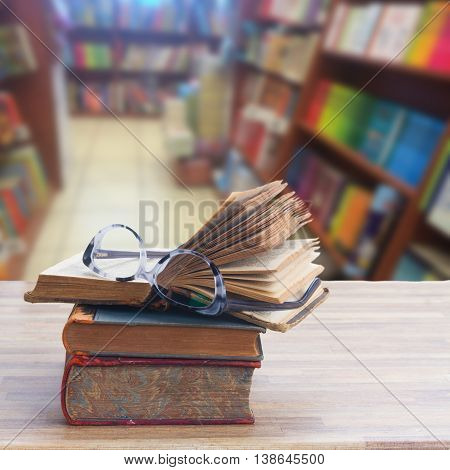 Stack of old books and glasses on wooden table desktop in bookstore