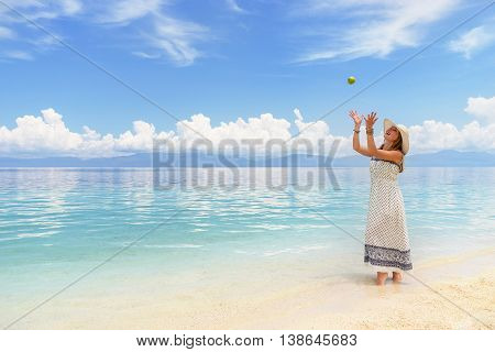 Youn europian woman in light dress and hat walking on white sand beach near calm amazing sea and playing with green apple at sunny day under blue cloudy sky.