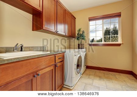 Spacious Laundry Room With White Appliances And Tile Floor