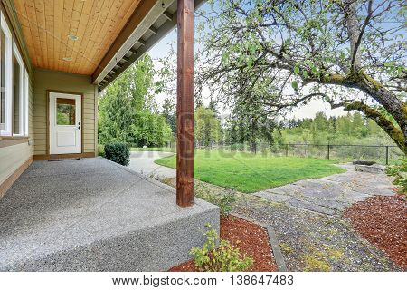 Small Empty Covered Porch With View Of Backyard Landscape