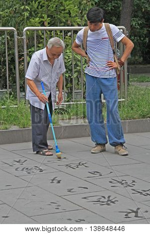 Chengdu China - June 14 2015: old man is writing Han characters on the ground with brush and water
