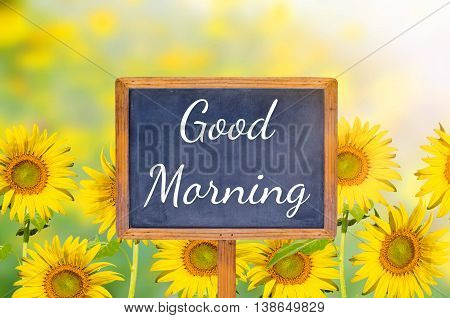 Good morning on blackboard with sunflower background