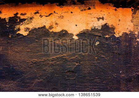 concrete wall with damaged plaster and the remains of the old bituminous paints