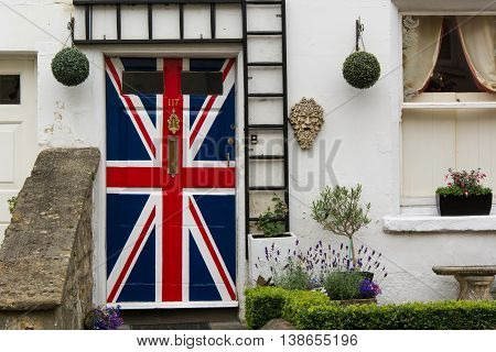 BATH SOMERSET UK - JULY 15 2016 Door painted with Union Jack flag. Front door of house painted in red white and blue of British flag