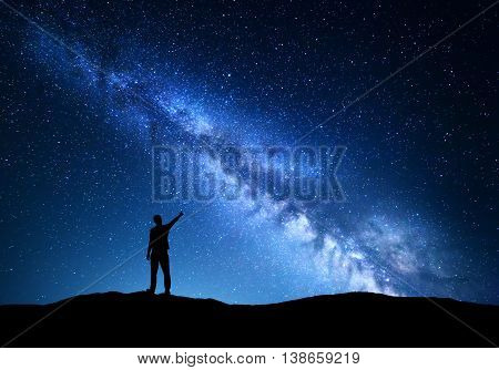 Milky Way. Silhouette of a standing man pointing finger in night starry sky on the mountain. Colorful night landscape with beautiful universe. Travel background with blue sky full of stars and amazing Milky Way