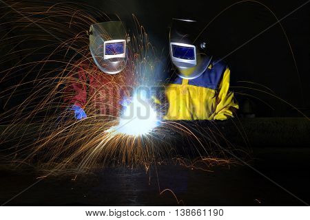 Industrial workers cutting and welding metal with many sharp sparks, Welder working a welding metal with protective mask and sparks