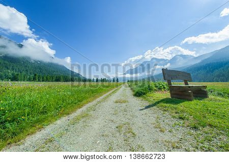 wiew of a mountain road with a bench
