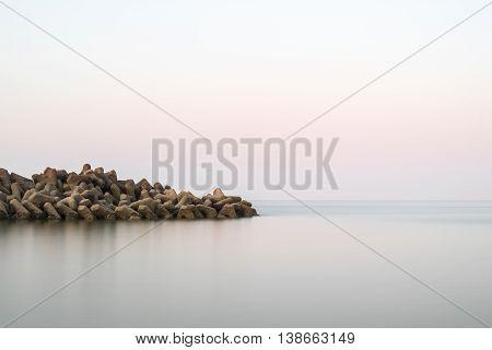 Beautiful Calm Landscape Of Rocky Outcrop Into Calm Sea