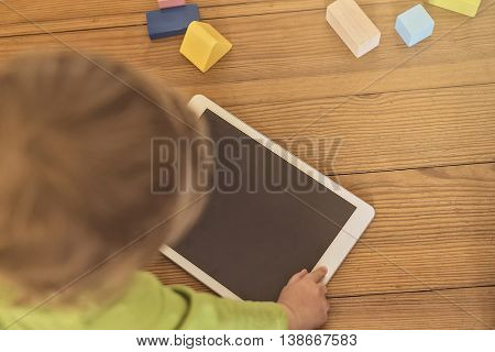 top view of a toddler playing with a tablet device on a wooden floor, wooden toys in the background